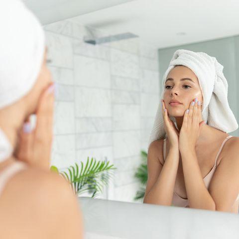 Eine Frau cremt nach der Dusche ihr Gesicht ein.