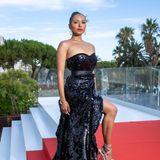 Wie man sich auf dem roten Teppich unter Palmen, hier vor dem Hotel Martinez, richtig präsentiert, zeigt Kat Graham im schwarzen Pailletten-Look von Pinko.