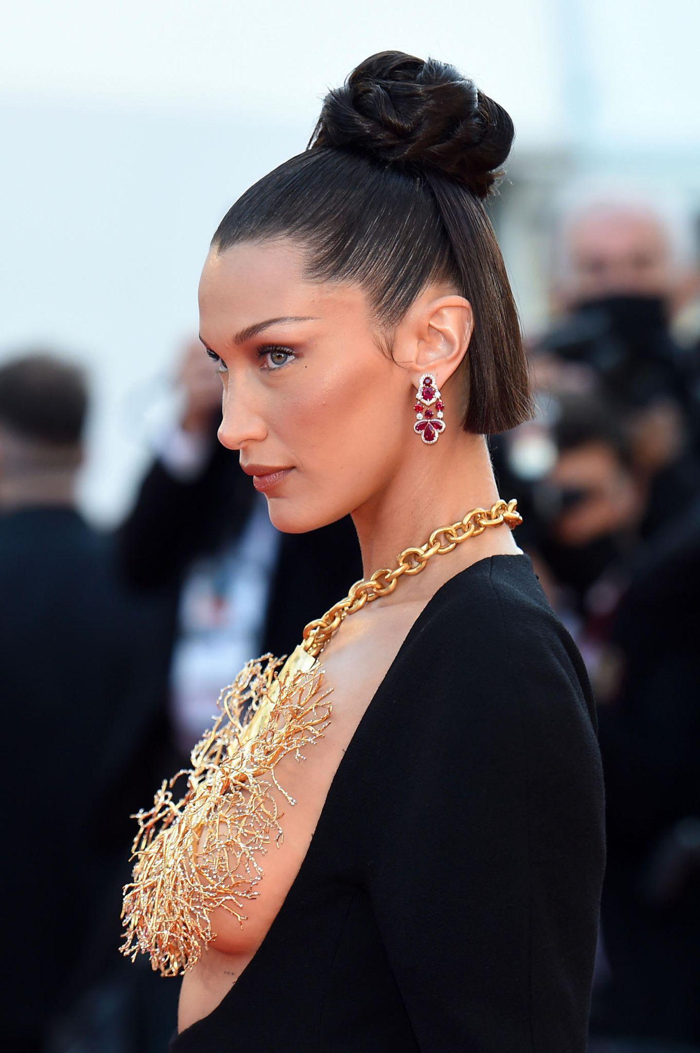 Auch wenn man bei diesem Look die Augen kaum vom XXL-Dekolleté mit Kette abwenden kann, begeistert Topmodel Bella Hadid mit perfekt konturierten Wangenknochen und einer grafischen Frisur.