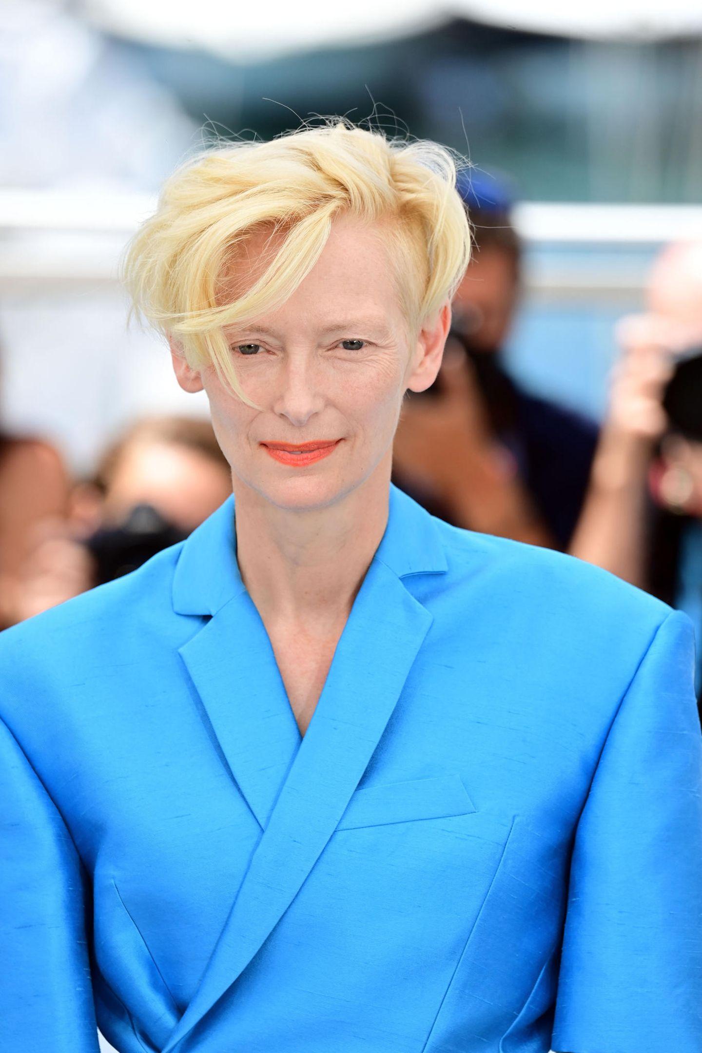 Tilda Swinton präsentiert einen frischen Look mit orangefarbene Lippen, die ihren blauen Anzug perfekt in Szene setzen.