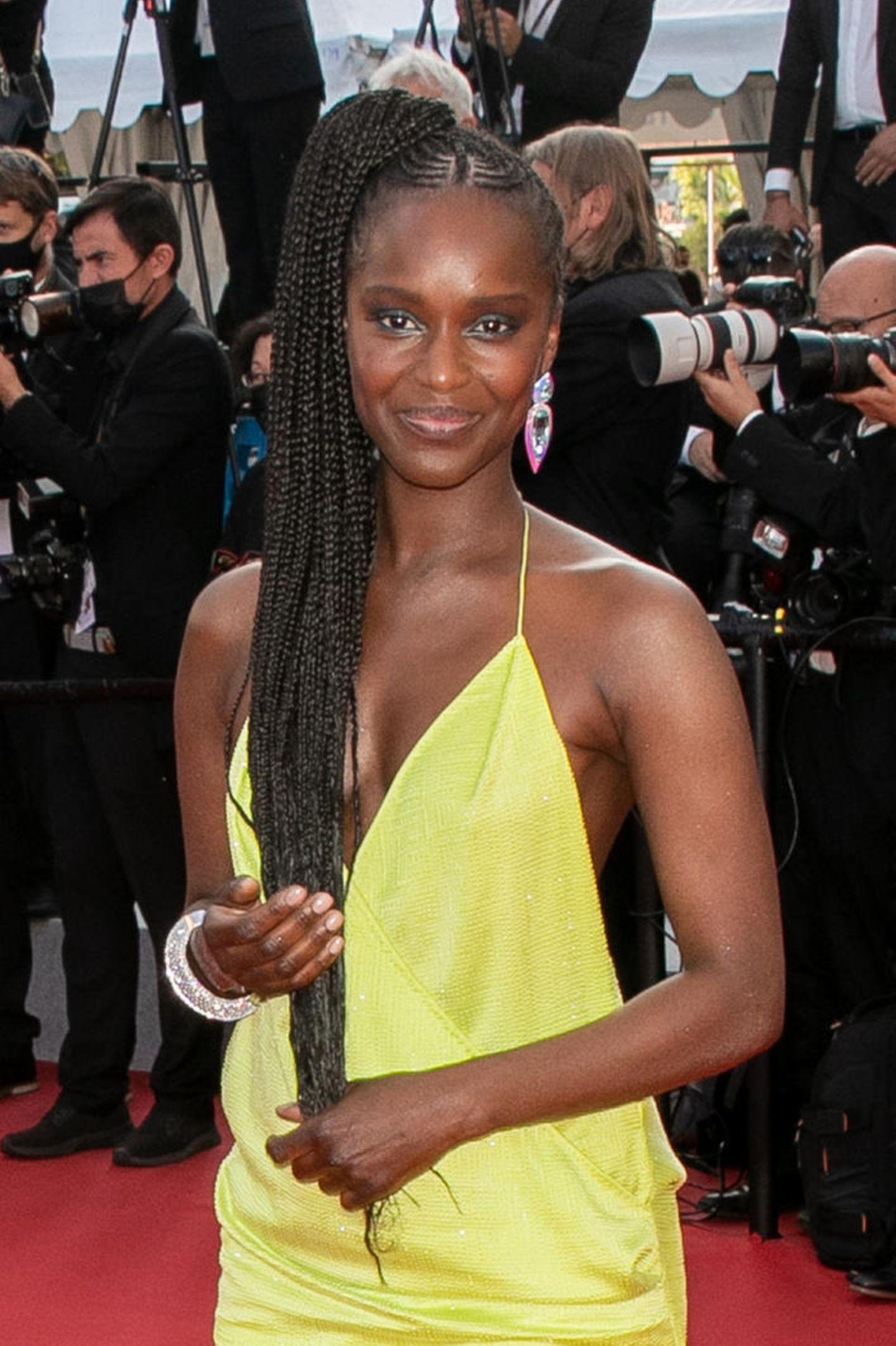 Fatou N'Diaye strahl in einem gelben Kleid mit V-Ausschnitt und trägt dazu zauberhafte Cornrows.