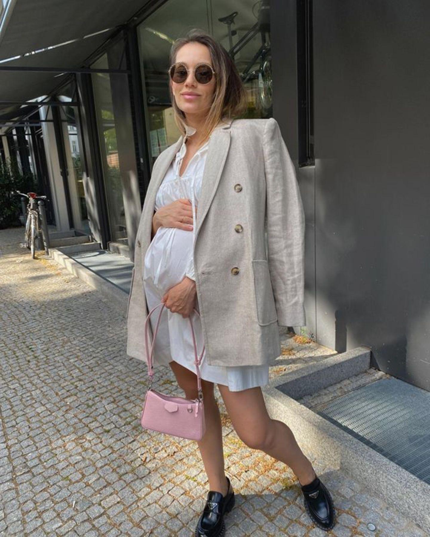 Endlich zeigt Model Anna Schürrle auf Instagram ihre Babykugel. Erst vor wenigen Tagen hat sie ihre Schwangerschaft auf Instagram bekannt gegeben. In diesem weißen Blusenkleid kommt ihr Bauch richtig toll zur Geltung. Dazu trägt sie ihren Leinenblazer lässig über die Schulter geworden und die rosafarbene Tasche gibt ihrem sommerlichen Look den letzten Schliff.