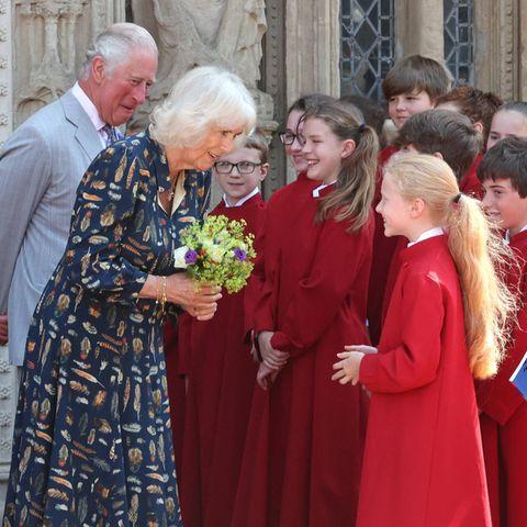 """19. Juli 2021  Was für ein herzlicher Empfang zum britischen """"Freedom Day""""! ImRahmen ihresdreitägigen Besuchs inDevonund Cornwall treffen Herzogin Camilla und Prinz Charles auf junge Chormitglieder der Kathedrale St.Peter in Exeter. Besonders Camilla ist angetan von der netten Begrüßung und nimmt fröhlich einen sommerlichen Blumenstrauß entgegen."""