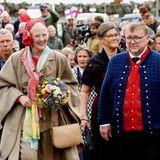 Am Tag zuvor wird Königin Margrethemit wehenden Fahnenin der Gemeinde Fuglafjørdur auf der Insel Eysturoy willkommen geheißen. Das Outfit der dänischen Royal ist heute ein besonderer Hingucker und sorgt bei ihrem Besuch für großen Anklang.