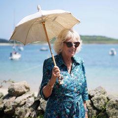 20. Juli 2021  Bei dieser traumhaften Kulisse bekommt Herzogin Camilla bestimmt Lust auf Urlaub. Die Herzogin ist heute zusammen mit ihrem Gatten Prinz Charles für einige Termine auf denScilly-Inseln. Mit Sonnenbrille und elegantem Schirm genießt Camilla den Gang entlangder Strandpromenade.