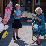 Das lässt sich Herzogin Camilla nicht zweimal sagen. Von einer Schülerin wird Camillawährend ihres Besuchs zum Vorlesen animiert und nimmt fröhlich das Buch entgegen.