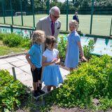 Vom Strand aus geht es für das Herzogenpaar weiter zur Five Islands Academy. Hierpräsentieren die Schüler:innen Prinz Charles stolz den eigenen Gemüsegarten und Charles lässt sich geduldig über denSchulhof führen.