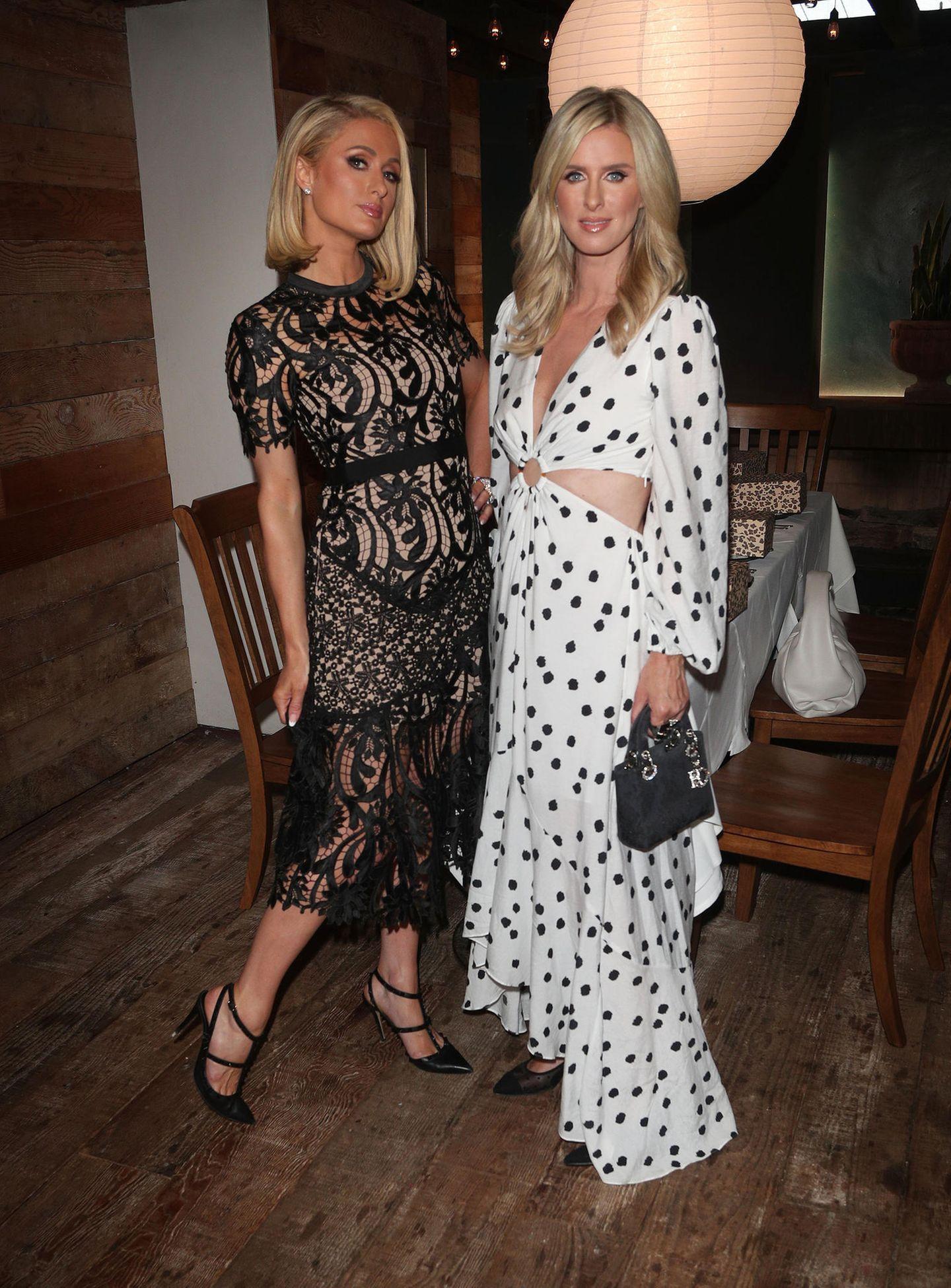 Hier liegt der Style wirklich in der Familie. Für eine Party in Santa Monica werfen sich Paris und Nicky Hilton in Schale. Paris wählt ein schwarzes Spitzenkleid, während Nicky auf ein sommerliches Polka-Dot-Kleid mit Cut-Outs setzt.