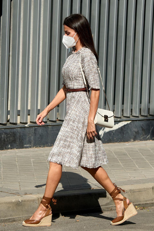 Schon fast herbstlich ist der Look von Königin Letizia, die sich auf dem Weg zum Meeting der Assoziation gegen Krebs befindet. Der Grund: Der Tweed-Stoff ihres Kleides vonAdolfo Domínguez, der schon jetzt für Style-Inspiration für kühlere Tage sorgt. Eine sommerliche Note bekommt der Look durch Letizias Espadrille Wedges vonUterqüe. Ein Modell, dasdie Royals im Sommer rauf undrunter tragen. Ihre weiße Schultertasche von Furla rundet den Look perfekt ab.