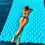 Carina Walz liegt im Bikini auf einer Luftmatratze auf dem Meer.