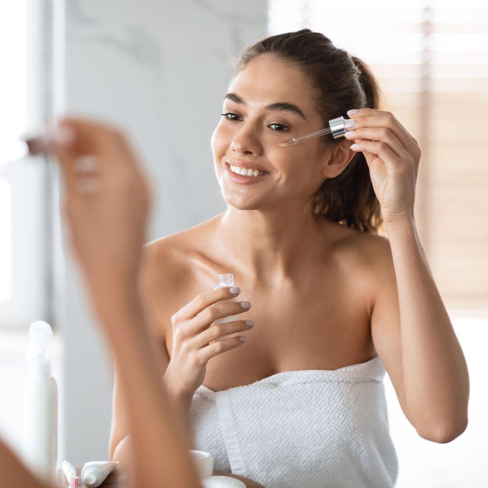 Schöne Frau im Handtuch trägt Serum mit Pipette auf das Gesicht auf