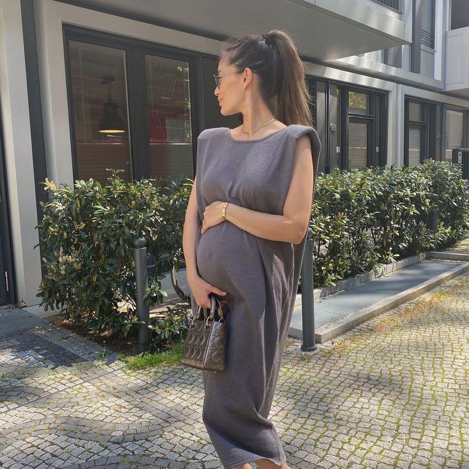 Anna Schürrle zeigt ihre Babykugel in einem sommerlichen Kleid.