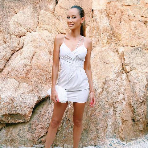 Alessandra-Meyer-Wölden posiert vor einer Steinmauer für ein Foto.
