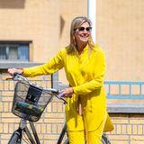 In ihrem sonnig-gelbenSommerlook mit langer Seidenbluse, 7/8-Hose und Fransengürtelist Königin Máxima bei einer Fahrradtour zum Kunstmuseum in Den Haag nicht zu übersehen.