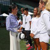 Herzogin Meghan zog mit diesem elegant-maritimen Look beim Tennisturnier in Wimbledon 2018 alle Blicke auf sich: Die extraweite Marlene-Hose und das blau-weiß gestreifte Hemd kombiniert sie perfekt mit dem sommerlichen Fedora-Hut.