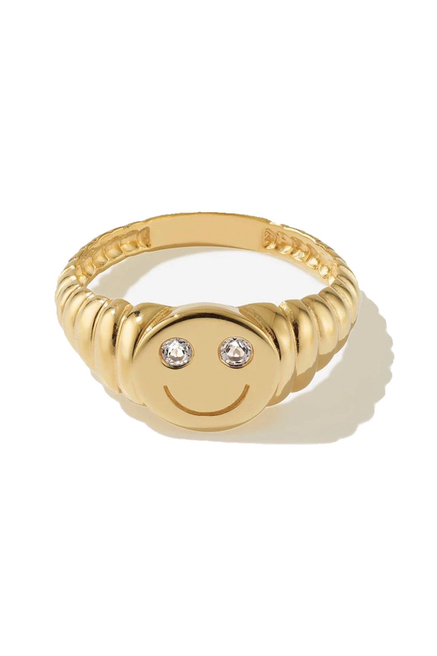 Na, wenn da mal keine gute Laune garantiert ist! Der Smiley-Ring aus vergoldetem 925 Sterling-Silber versüßt uns den Alltag und steckt uns mit seinem Lächeln direkt an. Was wollen wir mehr? Von Bruna, ca. 125 Euro.