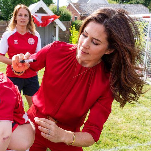 Prinzessin Mary unterschreibt auf dem Trikot eines Kindesbeim Besuch eines Fussballfestes in Rødovre im Juni2021.