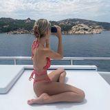 Leni Klum schaut durch ein Fernglas auf das Meer.