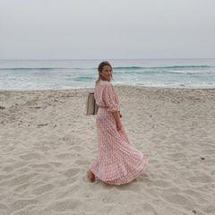 Laura Osswald steht im Maxi-Kleid am Strand.