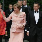 Angela Merkel und Joachim Sauer winken den Menschen bei einer Veranstaltung zu.