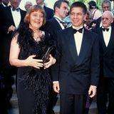 Angela Merkel und Joachim Sauer tragen Abendrobe bei einer Veranstaltung.