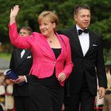 Angela Merkel winkt beim Ankommen mit Joachim Sauer den wartenden Menschen.