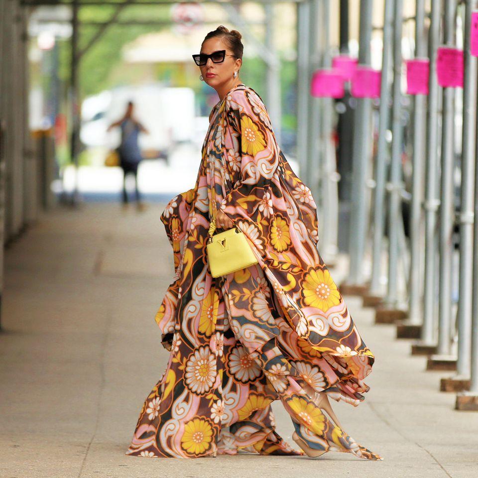 """Auf den ersten Blick hätte man Pop-Ikone Lady Gaga fast gar nicht erkannt. Schließlich scheint ihr Outfit diesmal gar nicht """"gaga-like"""". Imvoluminösen Blumenkleid und mit leuchtend gelber Handtasche von Louis Vuitton (Twist PM, rund 3000 Euro) zeigt sie sich in den Straßen von New York City. Ihre ikonischeCat Eye Sonnenbrille trägt die Sängerin natürlich auch."""