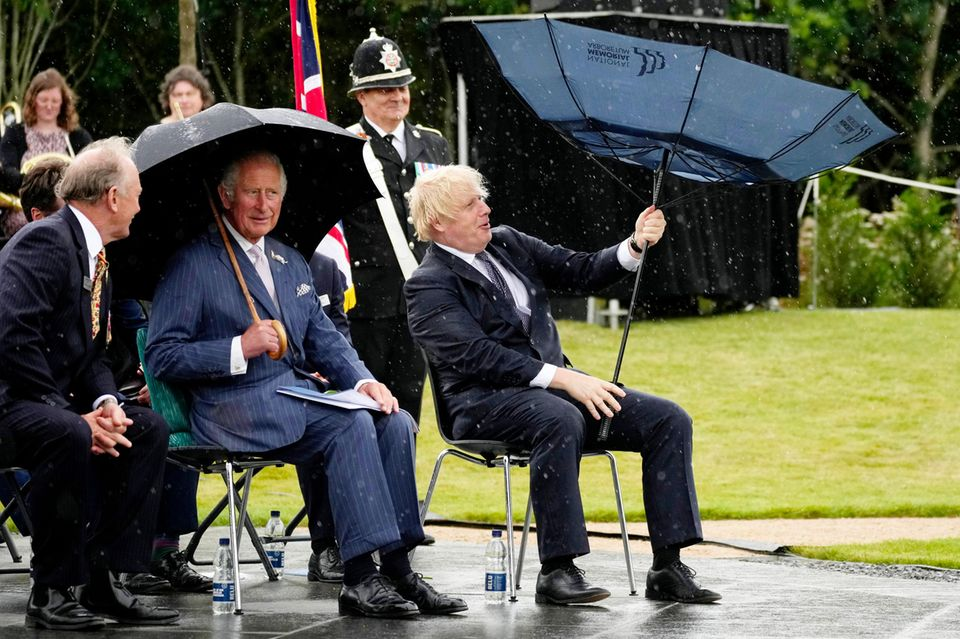 """28. Juli 2021  Prinz Charles ist heute bei der Einweihungsfeier des neuen Polizeidenkmals""""UK Police Memorial""""in Alrewas zu Gast und hat im Gegensatz zu seinem Sitznachbarn Premierminister Boris Johnson auch seinen Regenschirm fest im Griff. Da muss selbst der Polizist im Hintergrund schmunzeln und auch Charles konnte sich zuvor sein Grinsen nicht verkneifen."""
