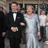 Joachim Sauer und Angela Merkel lachen in die Kamera.