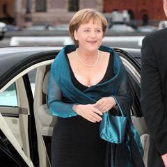 Angela Merkel verlässt das Auto und wird von einer männlichen Person empfangen.