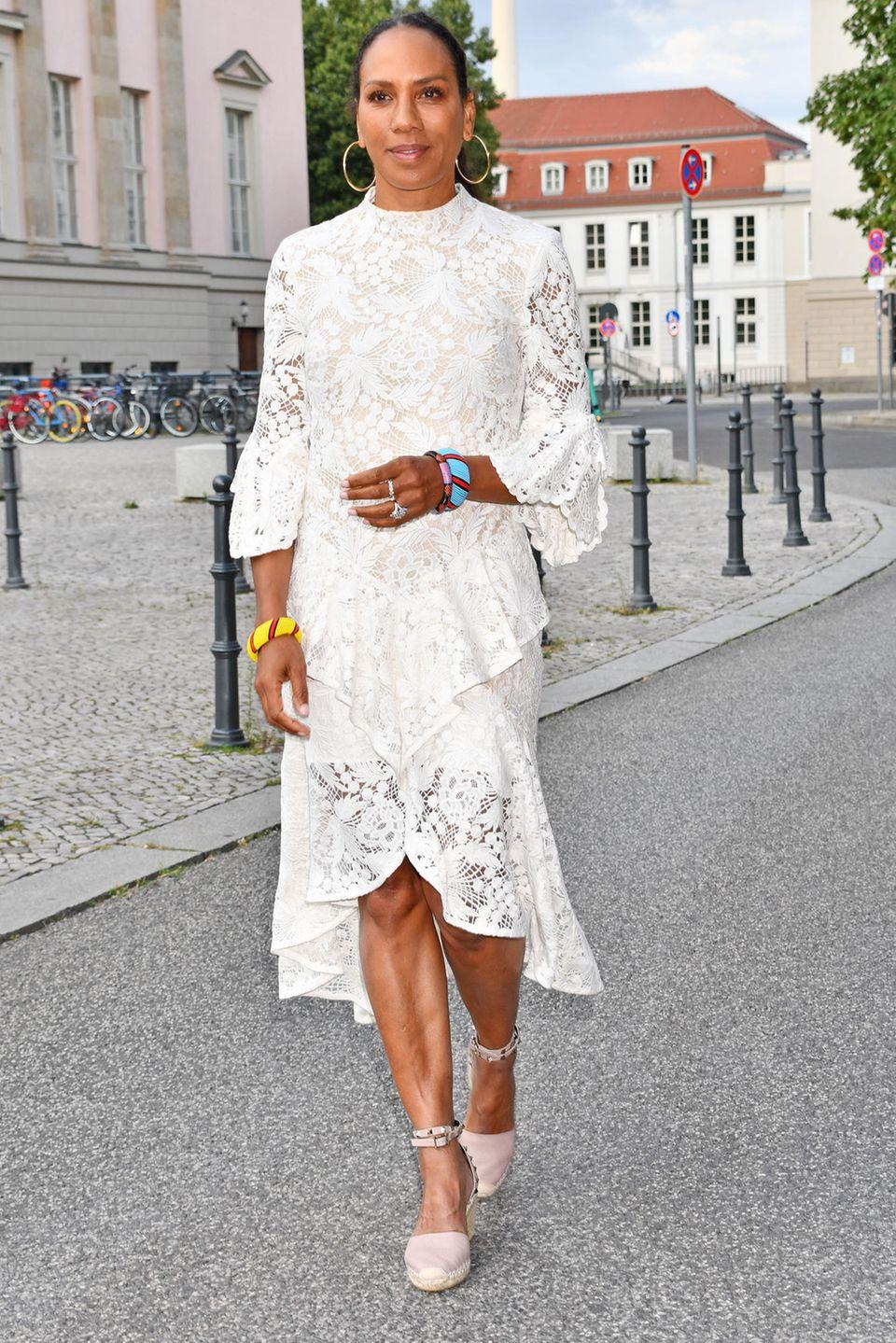"""Spitzen Look in Spitze! Im sommerlich weißenKleid begibt sich Barbara Becker auf den Weg zurDachterrasse des Hotel Rome in Berlin für das """"FRAUEN100""""-Event. Bei der Veranstaltung können sich inspirierende Frauen gegenseitig austauschen.IhreSchmuckwahl fälltdafür auf goldene Kreolen und bunteArmreifen, die perfekt ihrem Teint schmeicheln."""