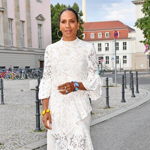"""Spitzen Look in Spitze! Im sommerlich weißenKleid begibt sich Barbara Becker auf den Weg zurDachterrasse des Hotel Rome in Berlin für das """"FRAUEN100""""-Event. Bei der Veranstaltung können sich inspirierende Frauen gegenseitig austauschen.IhreSchmuckwahl fälltdafür auf goldene Creolen und bunteArmreifen, die perfekt ihrem Teint schmeicheln."""