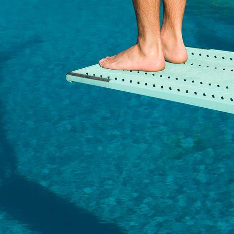 Tragischer Unfall: Füße eines Mannes, der auf Sprungbrett steht