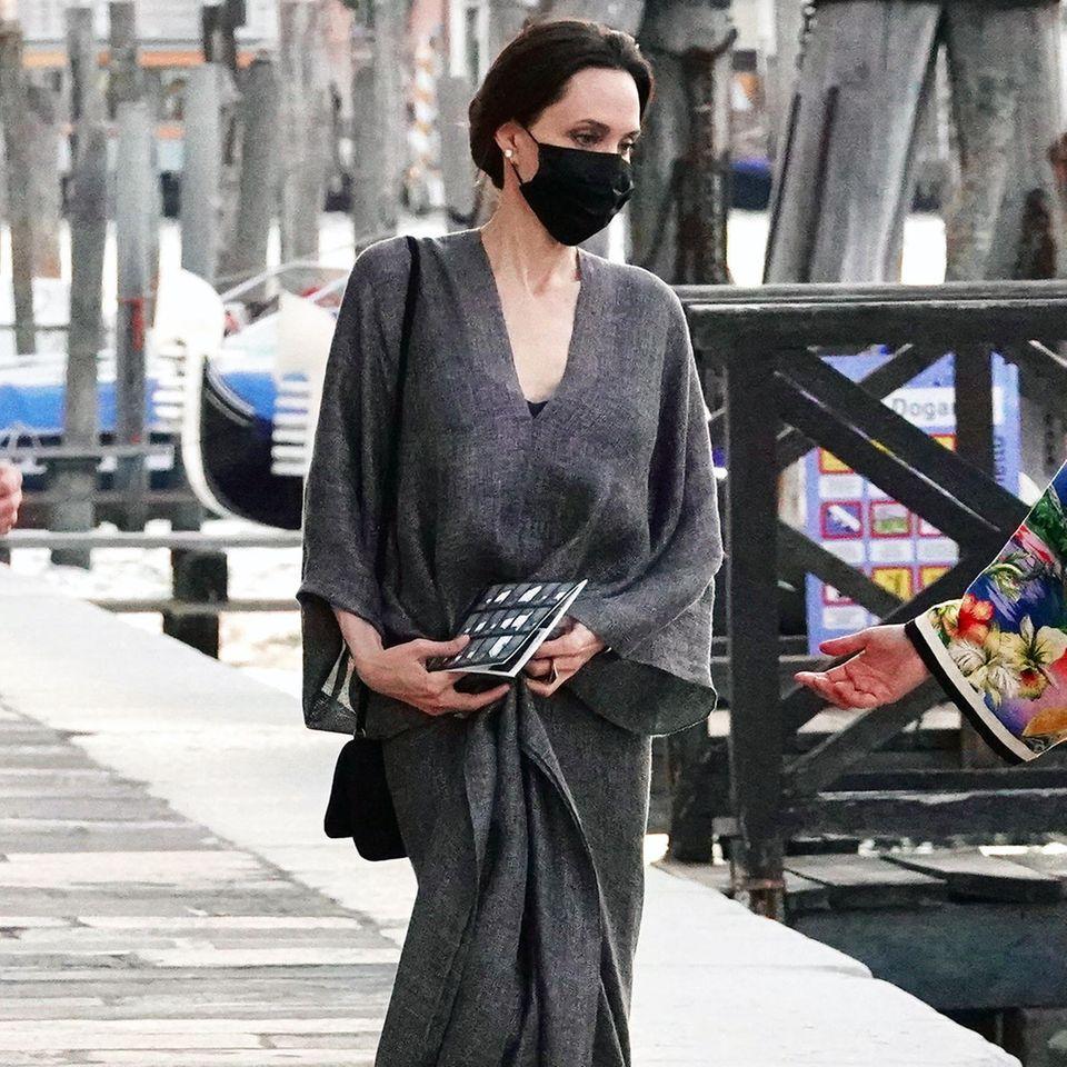 Wenn Angelina Jolie unterwegs ist, passiert das selten ohne das perfekte Outfit. Auch in Venedig zeigt sich die Schauspielerin edel und stilsicher, wie immer. Auf dem Weg zum Wassertaxi setzt sie auf einen bodenlangen Kaftan in dramatischem Grau und Sandaletten mit Blockabsatz von Chanel. Besonders passend: die Perlenohrringe zum eleganten Dutt.