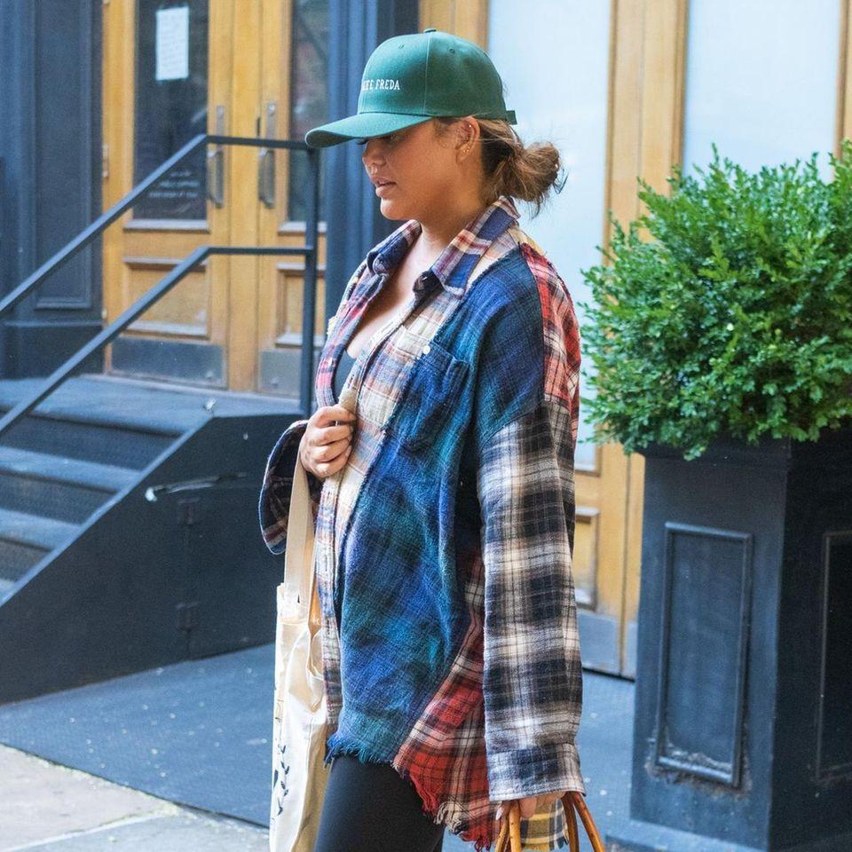 Leggings, Cap, Flanellhemd – ein ganz entspannter Look von Chrissy Teigen. Wenn da nicht ihre Handtasche wäre! Bei dem guten Stück handelt es sich nämlich um ein Design aus dem Hause Hermès, das in der Größe ähnlich teuer, wie ein Gebrauchtwagen ist. Ganz so leger geht es bei Chrissy dann also doch nicht her.