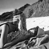 Gemeinsame Stunden als Familie sind Gold wert. So genießt Anna Schürrle ihren Strandtag zusammen mit Töchterchen Kaia. Ein schwarz-weiß Foto zeigt Mutter und Tochter auf einer Decke im Sand liegend – hinter ihnen ein Schutzwall aus Dünen. Liebevoll kuschelt Mama Anna darauf mit der Zweijährigen und schöpft in der Natur neue Kraft für den oft hektischen Familienalltag in Berlin.