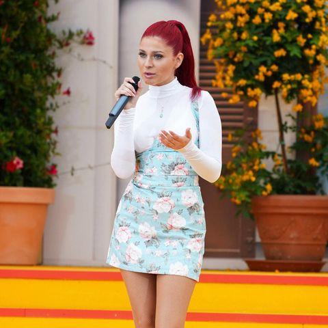 """Eye Candy: Für ihren Auftritt bei """"Immer wieder sonntags"""" im Europa-Park in Rust kombiniert Marie Reim ihre knallroten Haare kontrastreich mit einem weiß-rosigen Mini-Dress. Zuckersüß sind auch die rosafarbenen Plateau-Heels, auf denen sie gekonnt die Showtreppe herabschreitet."""