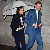 Prinz Harry und Meghan Markle laufen im Regen nebeneinander her.
