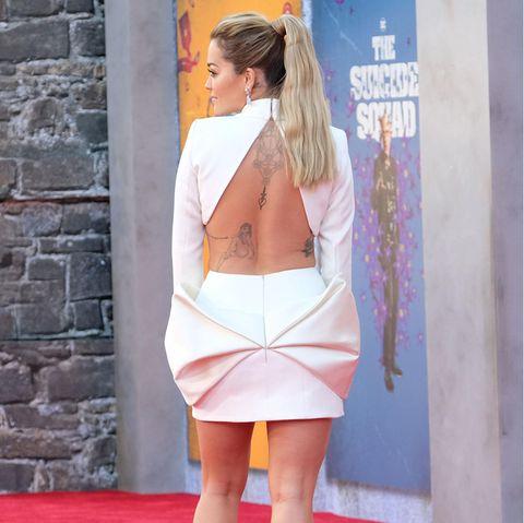 """Eine Kehrseite, die während der Filmpremiere von """"The Suicid Squad"""" alle Blicke auf sich zieht, ist die von Sängerin Rita Ora. In einem Mini-Kleid mit sexy Rückenausschnitt und einer überdimensional großenSchleife an Hüfte und Po tritt sie vor die Fotograf:innen."""