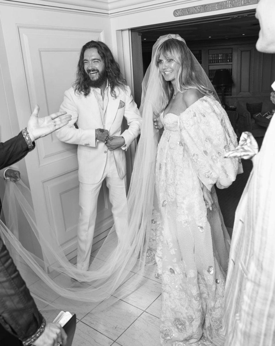 """Am ersten Augustwochenende 2019 gaben sich Heidi Klum und Tom Kaulitz in Italien das Jawort. Anlässlich ihres Hochzeitstages postet das Model nun ein bis dato unveröffentlichtesFoto der Feierlichkeiten bei Instagram. """"Alles Gute zum Hochzeitstag, mein Liebster"""", schreibt Heidizu der Aufnahme. Neben den lieben Worten an ihren Ehemann haben Heidis Fans aber vor allem Augen für das Brautkleid – eine ausladende Robe mit XXL-Schleier aus dem Couture-Haus Valentino. Es war eins von insgesamt drei Brautkleidern, die Heidi im Gepäck hatte."""