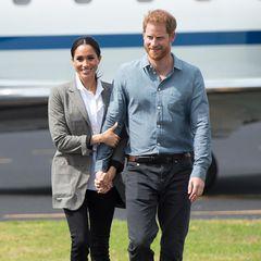 17. Oktober 2018  Ankunft im australischenDubbo. Beim Verlassen des Fliegers umschlingt Herzogin Meghan die Hand und den Arm ihres Liebsten. Prinz Harry scheint diese liebevolle Geste dankend anzunehmen. Gemeinsam strahlen sie um die Wette – aus einem besonderen Grund, denn Herzogin Meghan ist mit ihrem ersten Sohn Archie schwanger.