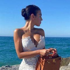 Georgina Rodríguez urlaubt derzeit mit der Familie im spanischen Marbella und verzichtet natürlich auch dort nicht auf ihre Luxus-Outfits. Zum weißen Spitzendress von Ermanno Scervino (ca. 3.000 Euro) kombiniert sie eine cognacfarbene Birkin-Bag aus Straußenleder sowie die Oran-Flats von Hermès. Alles in allem hat dieser Look den Wert eines guten Neuwagens.