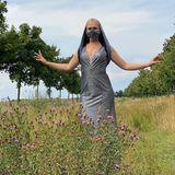 Sarah Knappik steht in einem Abendkleid und ungwöhnlicher Maske in einem Feld.