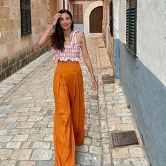 Zur weit fallenden Taillenhose in knallorange kombiniert Alessandra ein enges, gerafftes Sommertop. Ihre Haarpracht trägt sie ganz natürlich locker über die eine Schulter hängend – und wir träumen von lauen Sommernächten auf der Baleareninsel.