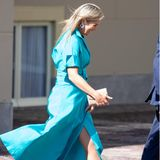 """Der Wind pustet an diesem Tag so stark, dass das glamouröse Kleid von Natan Couture fast zu viel von Königin Máximas nackten Beinen preis gibt. Das Kleid gehört zu ihren absoluten Lieblingen, sie trug es bereitsim Juni bei der Verleihung der """"Appeltjes van Oranje"""" (dt.: """"Äpfel von Oranien"""")."""