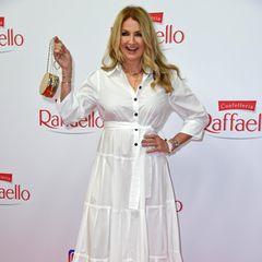 Frauke Ludowig wählt für das Event ein lässiges weißes Hemdblusenkleid von Marc Cain. Dazu kombiniert sie goldene Sandalen und eine goldene Tasche.