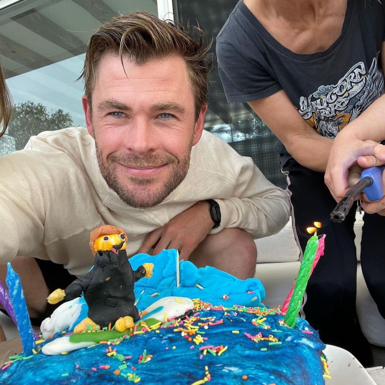 """Auf der Torte steht ein Männchen auf dem Surfboard im Meer – eine Hommage an Papa Chris, der leidenschaftlicher Surfer ist. Bunte Streusel und Kerzen runden den perfekten Geburtstagskuchen ab. """"Ich hatte einen wunderbaren Tag mit der Familie und wir haben es tatsächlich geschafft, 75 Prozent der Torte zu verschlingen, bevor der Berg aus Zucker in sich zusammenfiel"""", schreibt der Schauspieler zu seinem Instagram-Foto."""