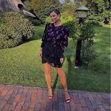 """Vor traumhaft idyllischer Kulisse posiert Moderatorin Laura Wontorra für ihre Instagram-Fans, schreibt unter das Bild """"Weddingvibes"""". In einem Blümchenkleid in Schwarz und Violett mit Puffärmeln und Raffungen macht sie als Hochzeitsgast eine tolle Figur. Schwarze Sandaletten und auffällige Creolen in Silber komplettieren den Look."""