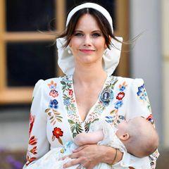 Prinzessin Sofia erscheint zur Taufe ihres jüngsten Sohnes Prinz Julian in einem weißen Kleid mit auffälligen Blumenmuster. Ein Haarband mit XL-Schleife ziert den Kopf der Dreifach-Mama, Perlenohrringe und ein pinkfarbener Lippenstift runden den Look ab.