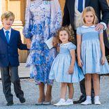Auch Nicolas von Schweden reiht sich in den Dresscode mit ein, trägt ebenfalls eine dunkelblaue Anzugsjacke. Allerdings in Kombination mit einer langen Anzugshose in Grau und einer hellblauen Krawatte. Seine Schwestern Adrienne und Leonore erscheinen im Partnerlook. Ihre Kleider stammenvon dem Label Trotters und bestechendurch ein blaues Blumenmuster, einen weißen Bubi-Kragen und kleinen Puffärmeln. Das Kleid gibt es jeweils für 118 Euro.